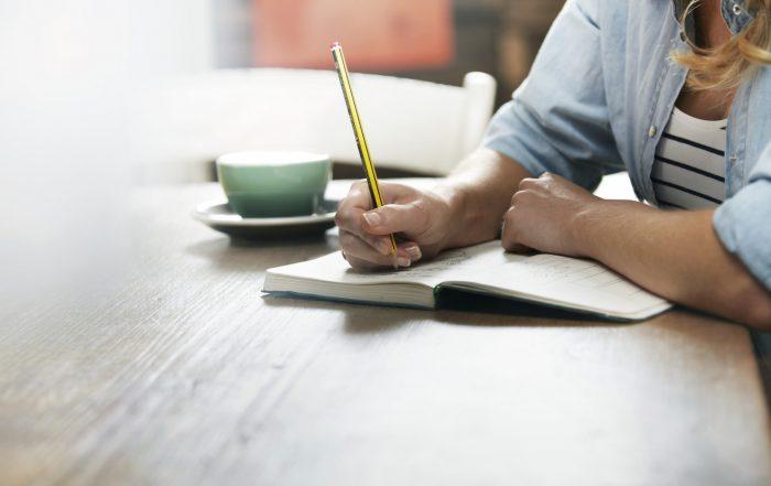 Woman Writing In A Coffee Shop